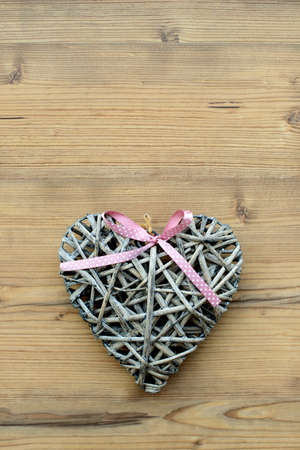 A heart made of straw on a wooden background Stock Photo