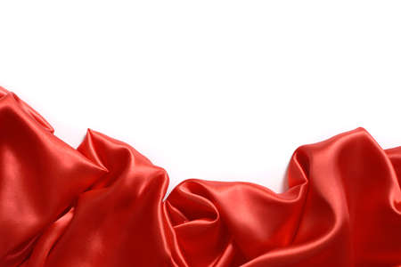 Close up of ripples in red silk fabric. Satin textile background with free copy space on white. Stock Photo