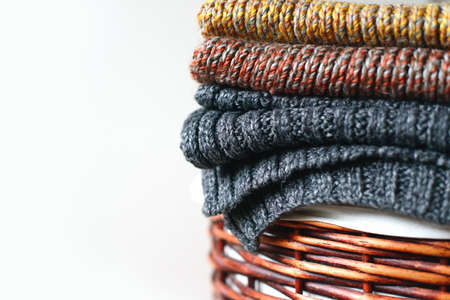 Pile of knitted winter scarfs on straw basket isolated on white background. Free copy space.