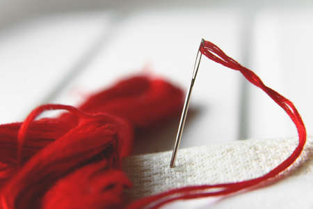 Needle in canvas with red thread for embroidery. Embroidery macro close up. View from above. Free copy space. 写真素材