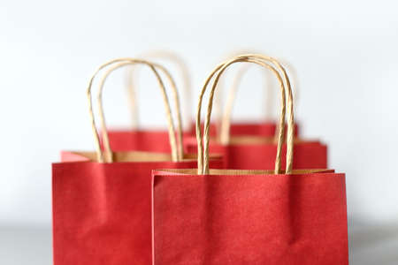 Red shopping bags from recycle paper isolated on white background. Black friday or Christmas sales.
