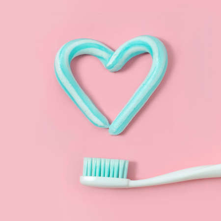 Toothbrushes and turquoise color toothpaste in shape of heart on pink background. Dental and healthcare concept. 免版税图像 - 103362493