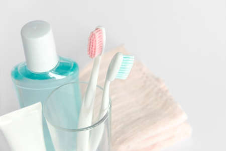 Toothbrushes, toothpaste, rinse and towel on white background. Dental and healthcare concept. Free copy space. Banque d'images