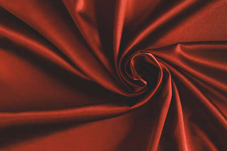 Close up of ripplesin shape of rose flower in red silk fabric. Satin textile background.