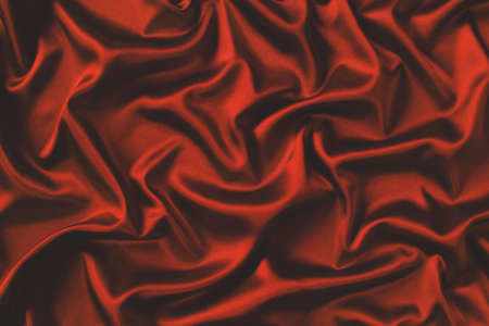 Close up of ripples in red silk fabric. Satin textile background.