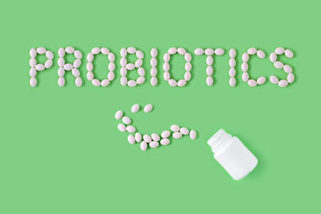 Probiotics word made of pills on green background. Flat lay, top view, free copy space. Stock Photo