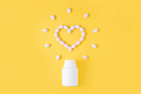 Pills in shape of heart dropped from bottle on yellow background. Flat lay, top view. Stockfoto