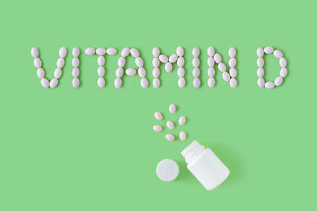 Pills dropped in shape of words vitamin D from bottle on green background. Flat lay, top view. Health care and medical concept. Banco de Imagens
