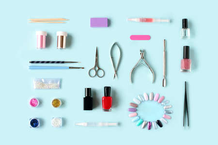 Set of various manicure and pedicure tools and accessories on light blue background. Top view.