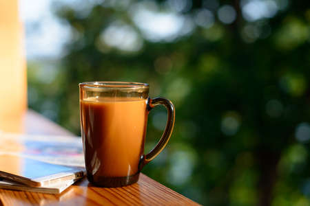 Cup of coffee and cellphone on the windowsill over blurred forest background at sunny summer day. Free copy space.