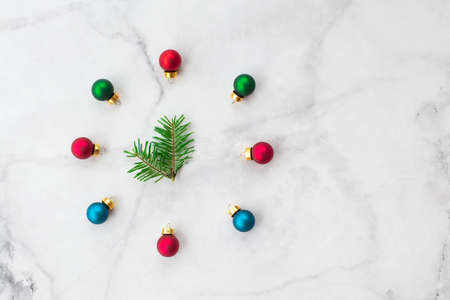Stylized Christmas clock made of fir-tree branch with blue and red ball toys on marble background. New Year and Christmas celebration concept. Flat lay, top view.
