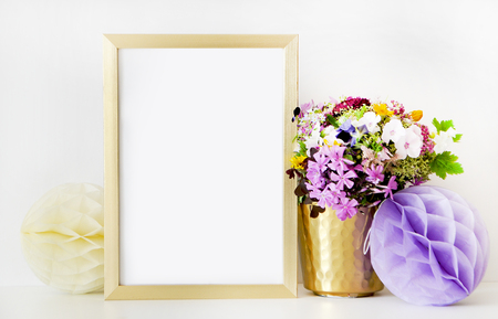 Gold frame mock-up, and white wall with gold vase, and flowers. Place work Stock Photo