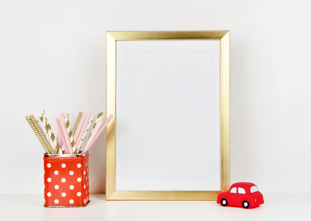 Gold frame mock up and toy red car, vase red and polka dots pattern. vintage Stock Photo