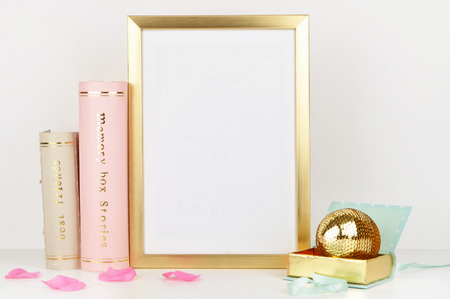 Gold frame mock-up, and white wall with gold book, and woman things. Place work