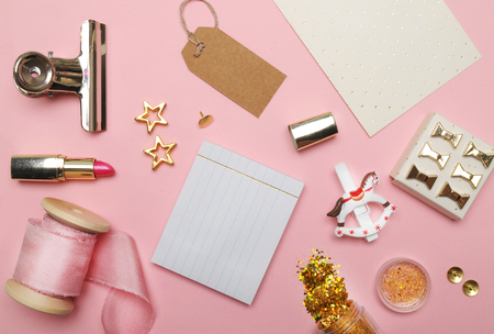 Stationery objects on desk. Flat lay. Accessories on the table, woman desk top. View top table, background mock up. Silk ribbon pink. Stock Photo
