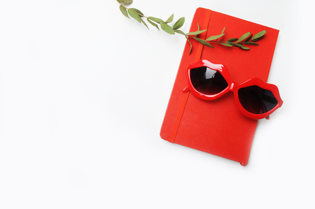 Flat lay, top view trendy feminine background. Red notebook and summer red glasses. Stock Photo