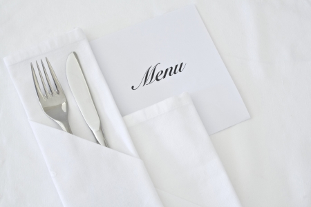 White linen table place setting with menu