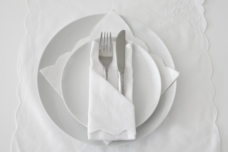serviettes: Table place setting in white with linen, plates and knife and fork