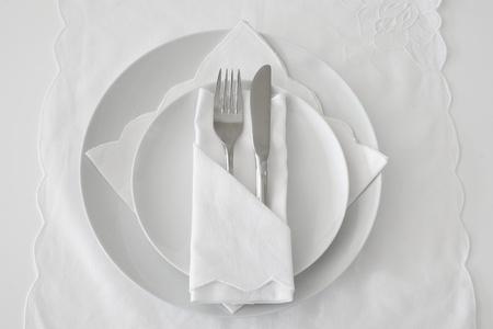 Configuración de lugar de la tabla en blanco con ropa de cama, placas y cuchillo y tenedor