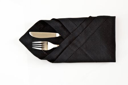 Knife and fork wrapped in a black napkin isolated on a white background