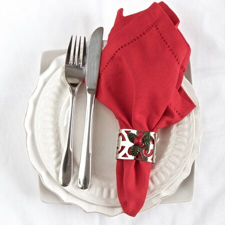 white napkin: Silverware with red napkin and white plates with a Christmas theme