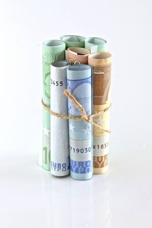 Euro Crisis. Euro bills rolled up and tied with string . Money is tied up concept photo