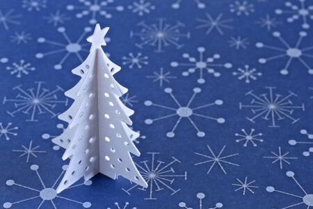 White Christmas Tree on blue snowflake background with space for text photo