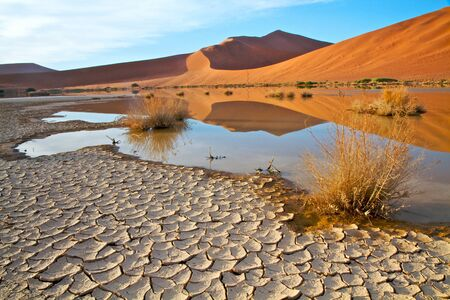 sossusvlei: Cracked earth and red dunes with water reflections in the Namibian Landscape Stock Photo