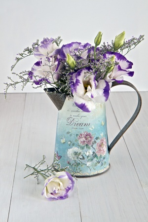 arrangement: Vintage tin jug with bunch of flowers Stock Photo