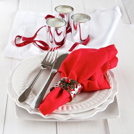 plate setting: Table setting with silverware, red napkin, candles and decoration for Christmas