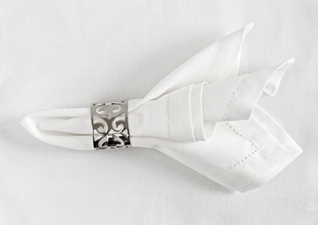 napkins: Table place setting of linen napkin and silver napkin ring