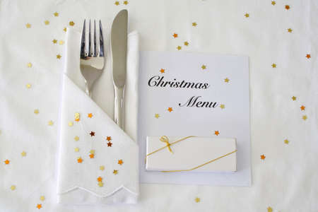Knife and fork with Christmas menu on white linen with gold stars photo