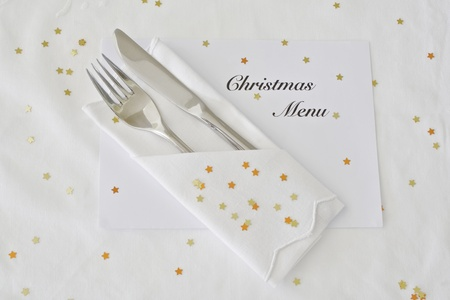 Knife and fork on white linen with Christmas menu and god stars photo