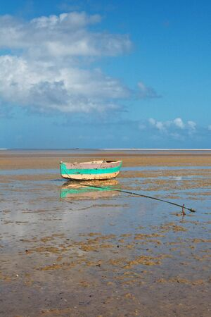 Tropical beach with old fishing boat