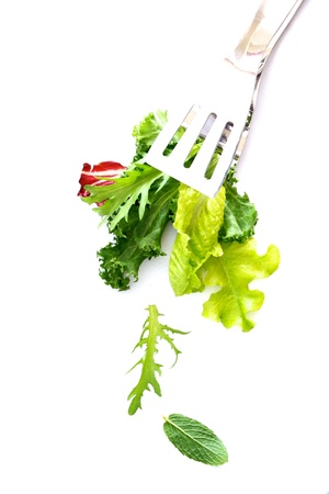 Fresh salad leaves and herbs isolated on white background