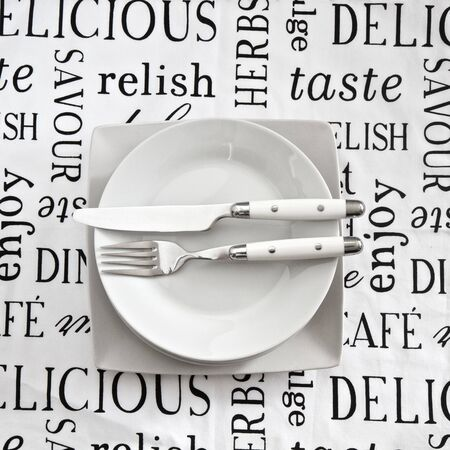 Table setting on printed tablecloth cith cutlery and plates