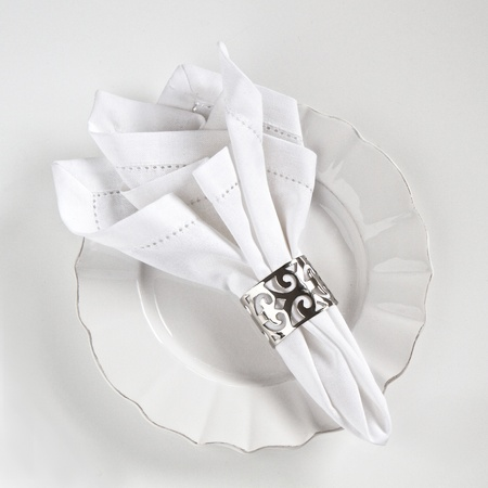 dinnerware: Table place setting with white linen serviette and silver ring Stock Photo