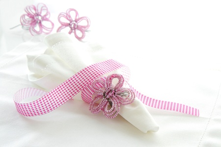 White linen serviette with pink beaded napkin ring on a white background with space for text