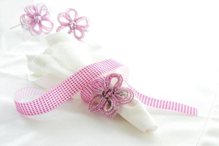 serviette: Wit linnen servet met roze kralen servetring op een witte achtergrond met ruimte voor tekst