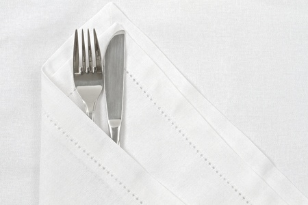 serviette: Knife and fork with white linen serviette and space for text