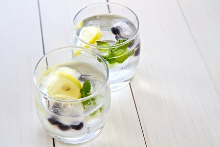 Ice cubes with fruit and mint in a glass of water with space for text