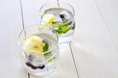 Ijsblokjes met fruit en munt in een glas water met ruimte voor tekst