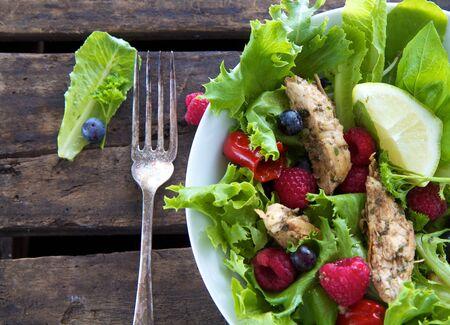Salade met kip en bessen tegen een rustieke achtergrond
