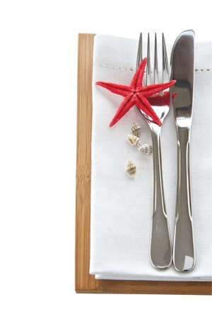 plate setting: Knife and fork with napkin and starfish for a beach table setting isolated on white