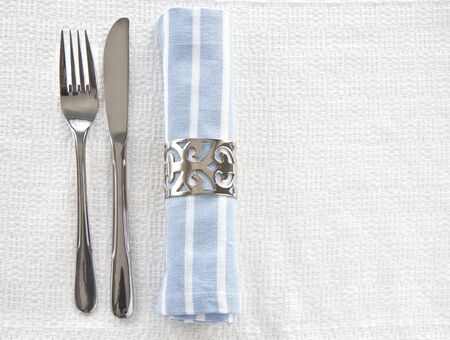 Table setting with blue an white striped napkin on textured linen tablecloth with space for text