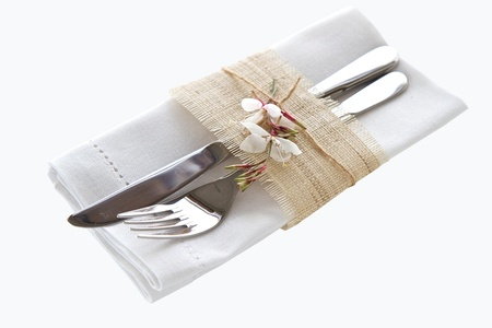 restaurant setting: Knife and fork with napkin isolated on white background Stock Photo