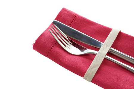 Knife and fork with pink napkin isolated on white background photo
