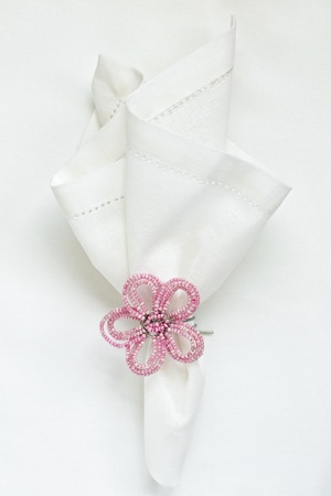 napkin: White linen napkin with beaded napkin ring Stock Photo