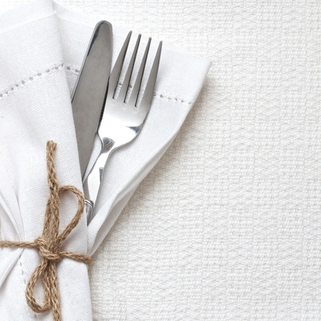 Knife and fork with white linen with up with string  Standard-Bild