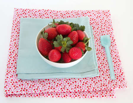 Strawberries in a bowl with napkin and spoon
